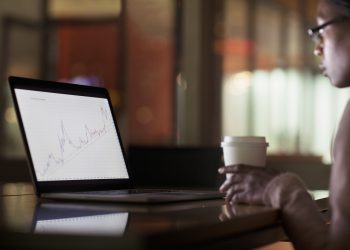 Woman viewing laptop screen with graph diagram