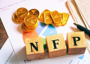 """Text """"NFP"""" on wood cube with gold bar and newspaper on the table, economic data concept"""