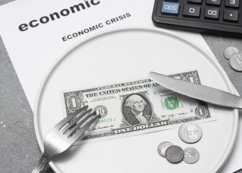 Economic crisis. One paper dollar with a fork and knife on a white plate Dividing the budget. Concept of the global financial crisis. Lack of money for food.