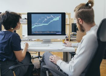 Anonymous businesspeople analyzing a stock market investment graph together in the office